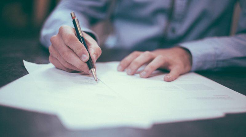 Un homme signant des documents chez le notaire
