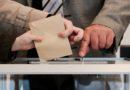 Un électeur glissant son bulletin de vote dans les urnes.