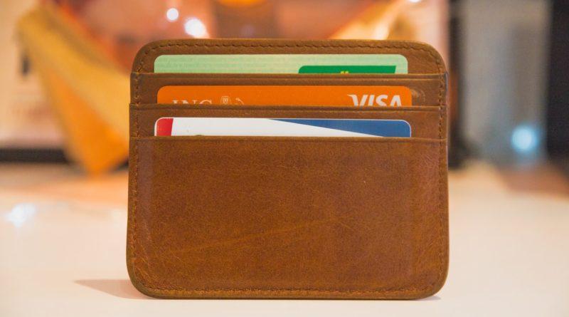 Portefeuille marron avec carte bancaire à l'intérieur.