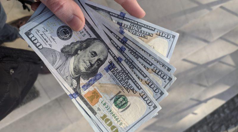 Un homme tenant des billets de 100 Dollars en main.