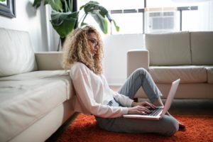 Une jeune fille assise au sol dans son appartement avec un ordinateur portable sur les pieds (Crédits : Unsplash).