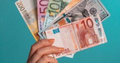 Une main de femme tenant des billets d'euros.